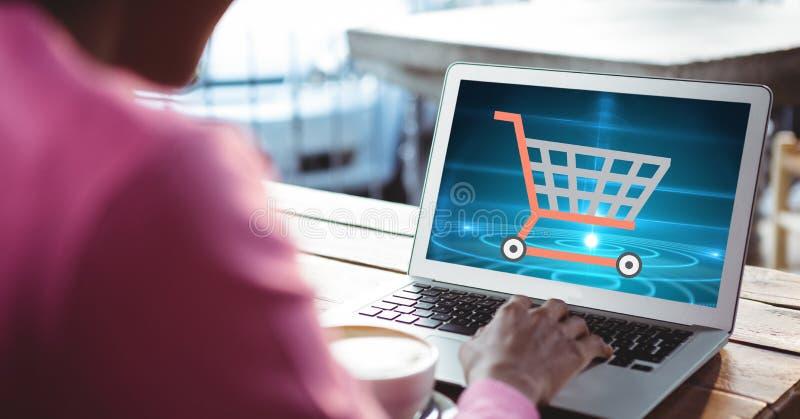 Image cultivée de femme faisant des emplettes en ligne utilisant l'ordinateur portable images stock