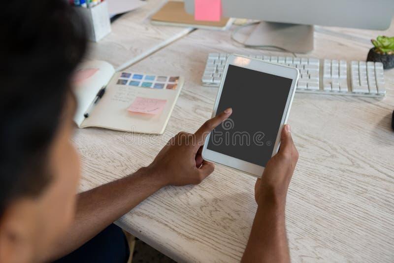 Image cultivée de l'homme à l'aide du comprimé numérique dans le bureau photographie stock libre de droits
