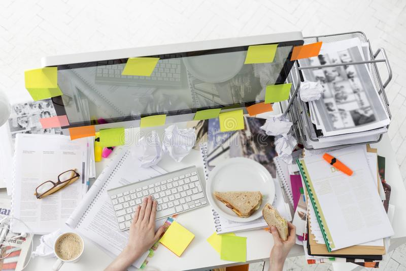 Image cultivée de l'homme d'affaires prenant le petit déjeuner tout en travaillant sur l'ordinateur images libres de droits