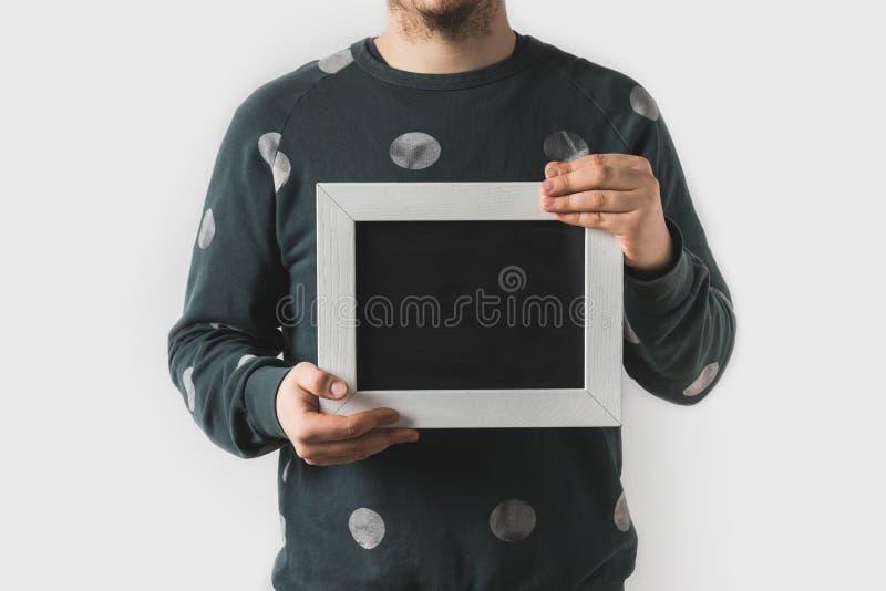 image cultivée de l'homme tenant le conseil noir vide photographie stock