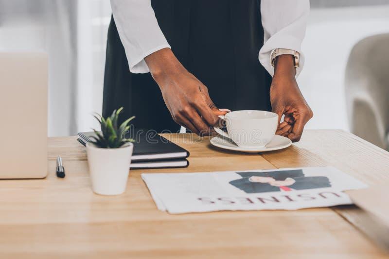 image cultivée de la femme d'affaires élégante d'afro-américain mettant la tasse de café sur la table dans le bureau images stock