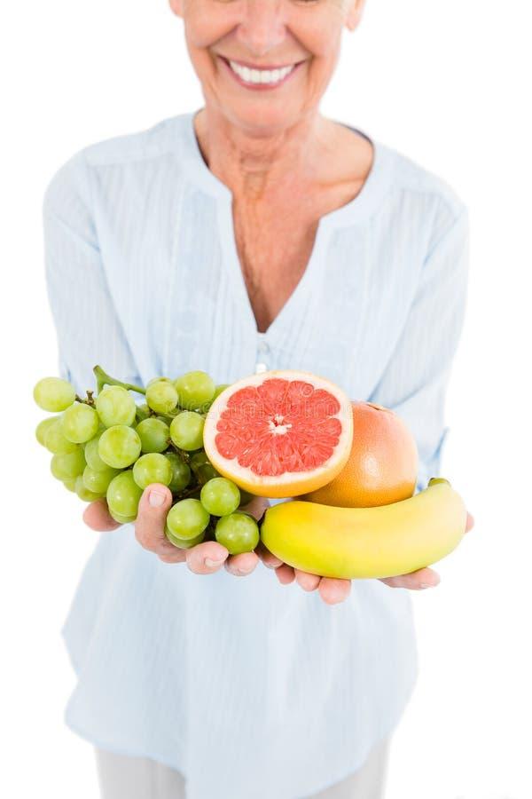 Image cultivée de la femme mûre de sourire tenant des fruits photo stock