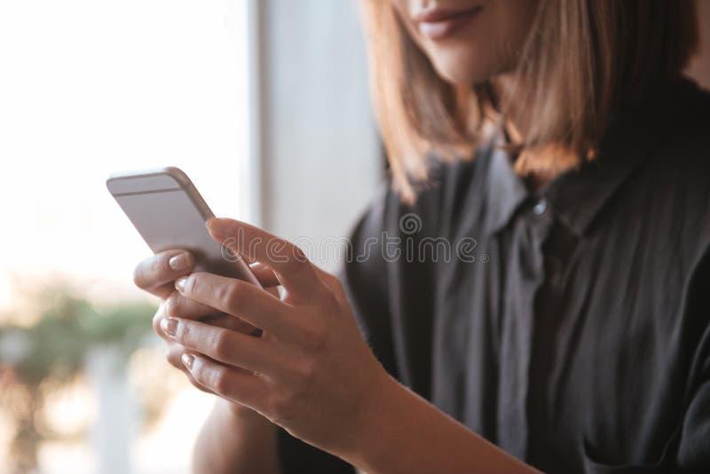 Image cultivée de la jeune femme à l'aide du téléphone portable image stock