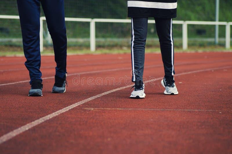 Image cultivée de la jeune position de sportif et de femme au-dessus de la profondeur du fond de champ image stock