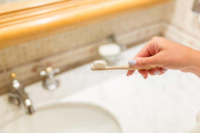 Image cultivée de la main attrayante de femme appliquant la pâte dentifrice sur la brosse à dents dans la salle de bains Concept  photographie stock libre de droits