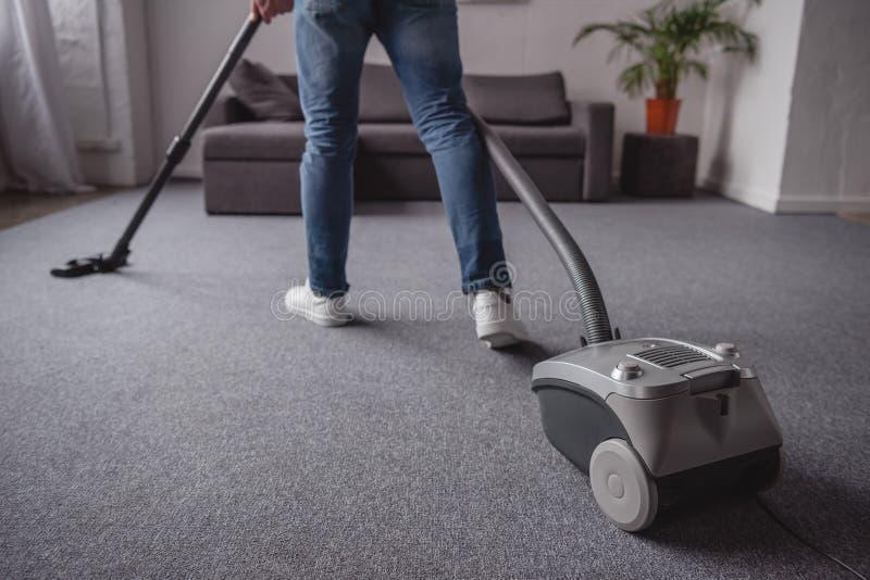 image cultivée de tapis de nettoyage de l'homme avec l'aspirateur photos stock