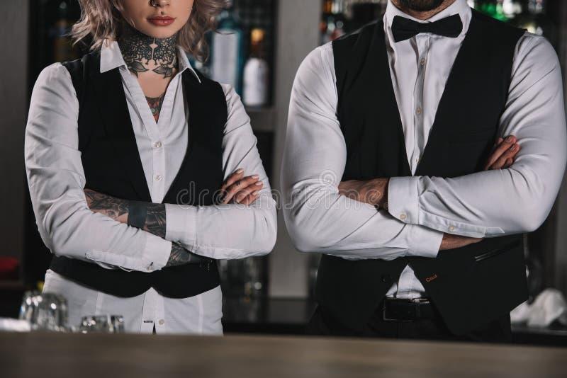 image cultivée des barmans féminins et masculins se tenant avec les bras croisés photos libres de droits