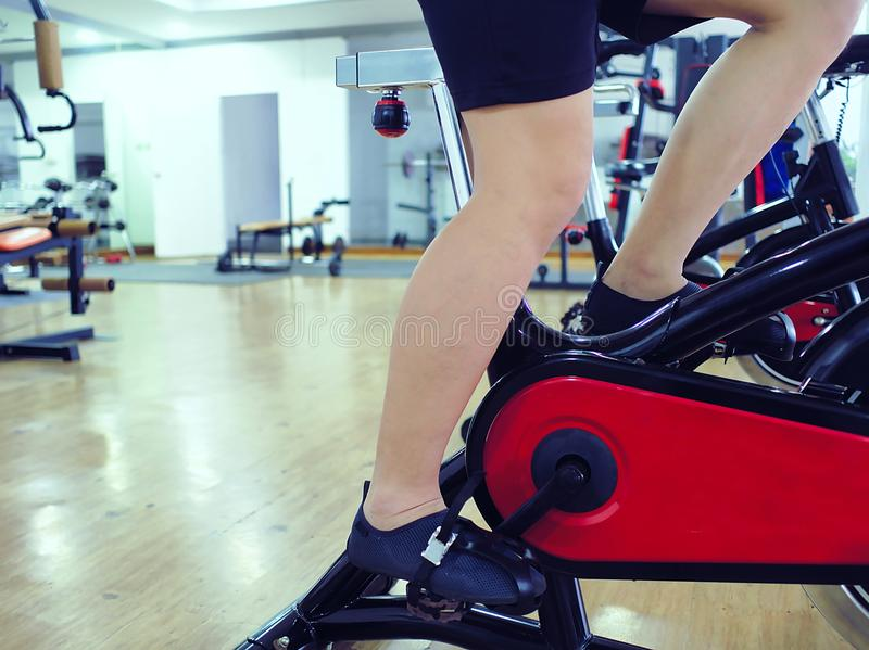 Image cultivée des jambes du jeune homme en bonne santé s'exerçant sur la machine de vélo au gymnase de sport Concept de forme ph photo stock
