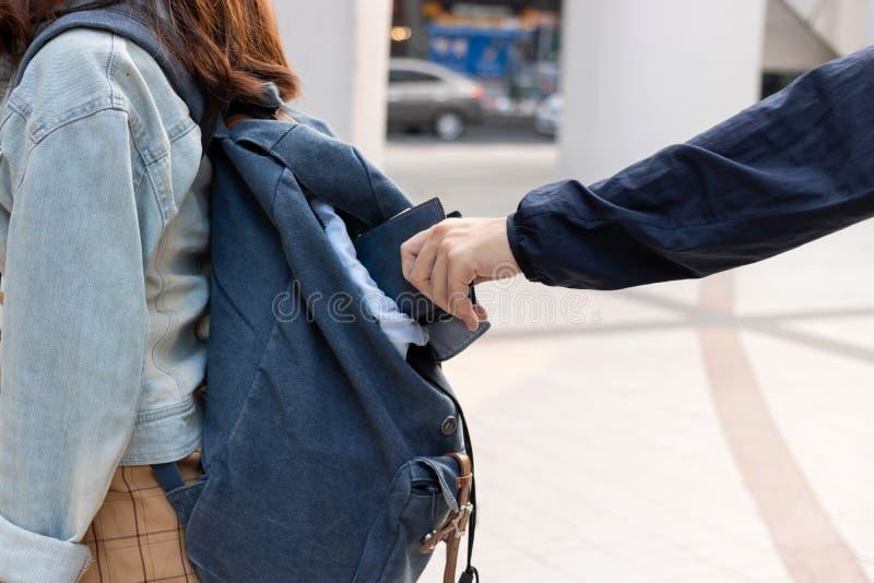 Image cultiv?e des mains du voleur de pickpocket volant le portefeuille du sac ? dos de la fille de touristes images stock