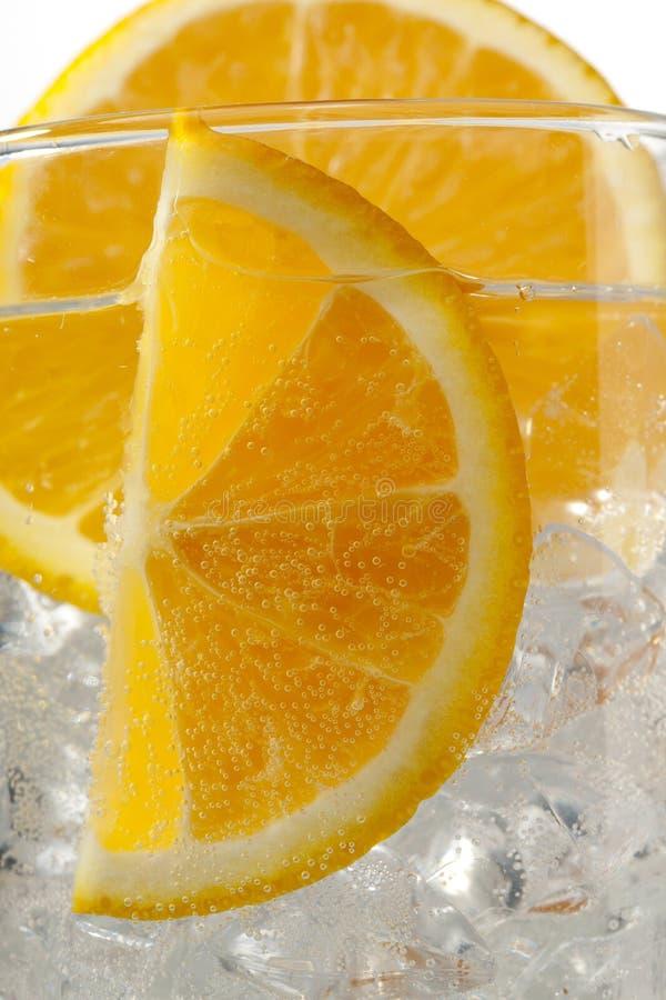 Image cultivée des parts oranges avec des glaçons. image stock