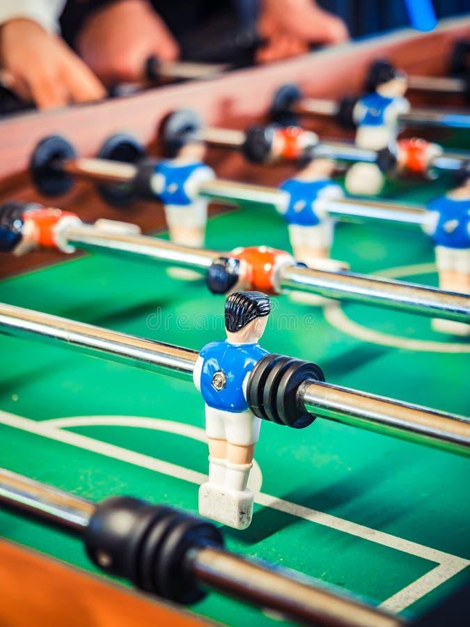 Image cultivée des personnes actives jouant le foosball plaers du football de table Les amis jouent ensemble au football de table images libres de droits