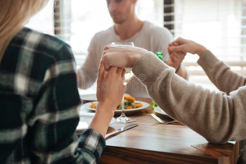 Image cultivée des personnes tenant des mains et la prière photographie stock