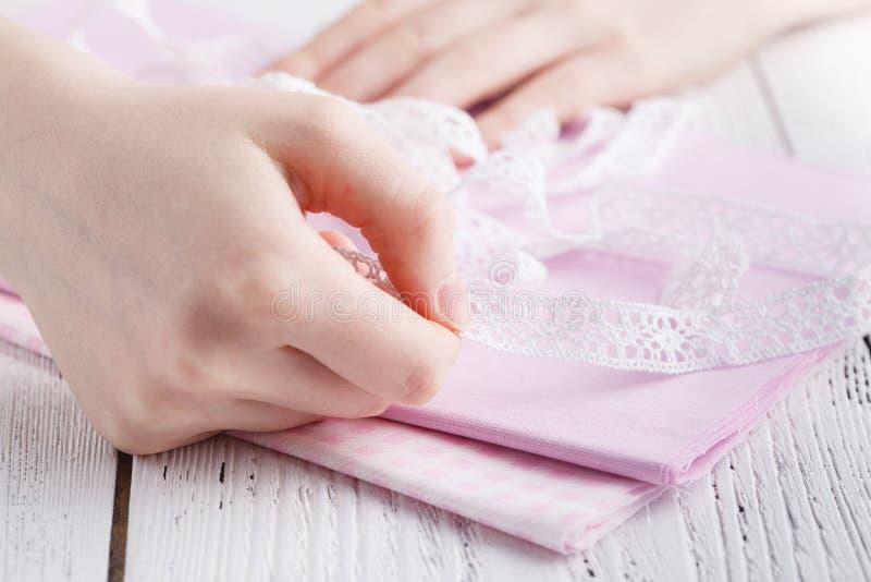 Image cultivée du beau jeune concepteur travaillant avec les croquis et la bande de mesure dans le salon de couture image stock
