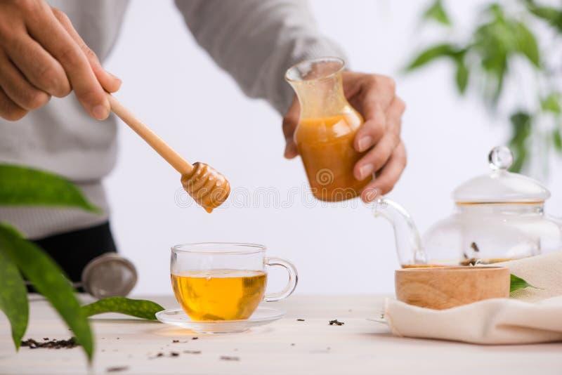 Image cultiv?e de miel de versement d'arista dans la tasse de th? images stock