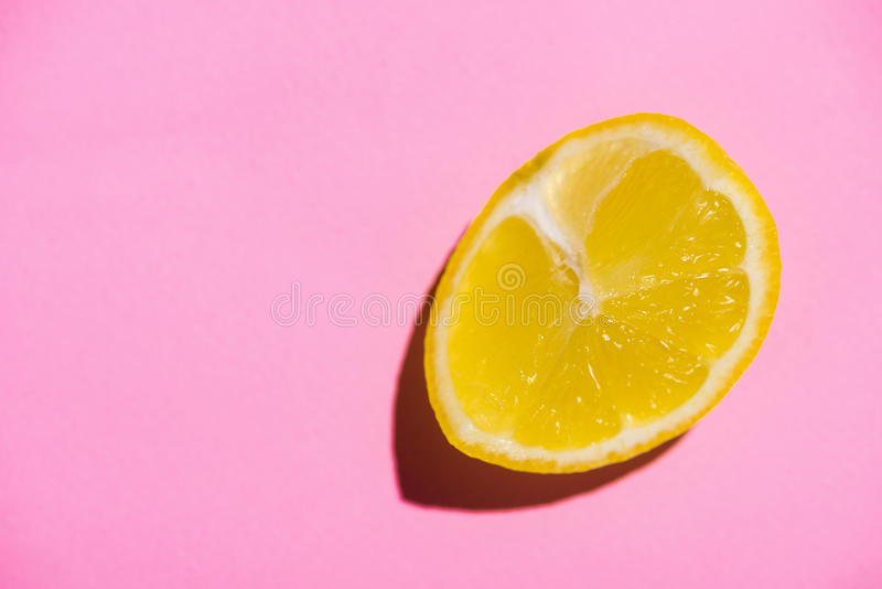 Image of cut half lemon on on a pink background. Minimal concept. Flat lay royalty free stock images