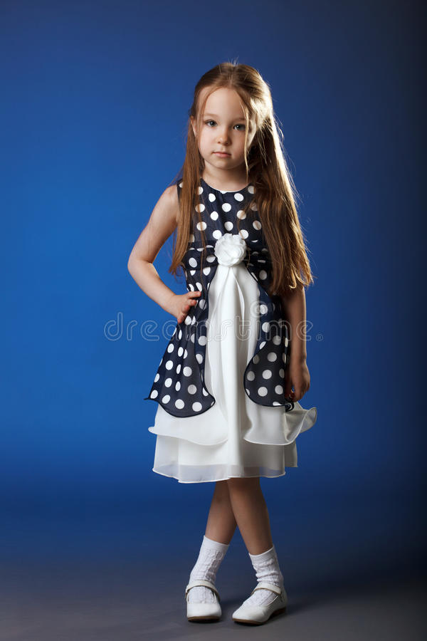 Image of cute girl posing in blue polka dot dress. On blue background royalty free stock image