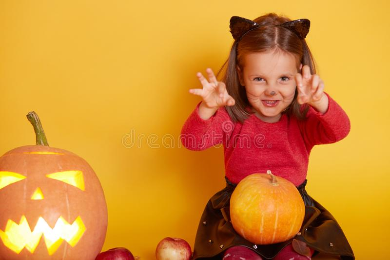 Image of cute little girl wearing red sweater and black skirt, posing with cat ears and mustache, scaring people in front of her, stock photos