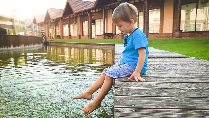 Photo of cute 3 years old little boy sitting on the riverebank at water canal in old town and splashing water with feet. royalty free stock photography