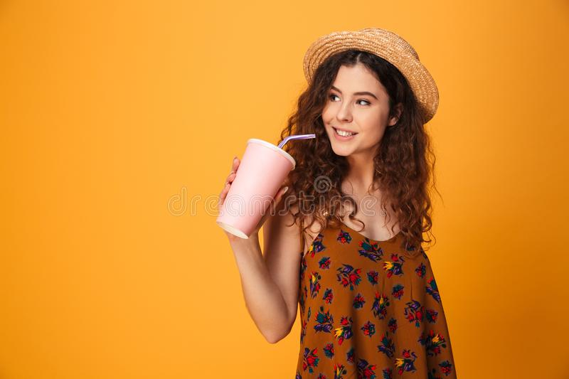 Cute young woman drinking aerated sweet water. Image of cute young woman standing isolated over yellow background. Looking aside drinking aerated sweet water stock photos