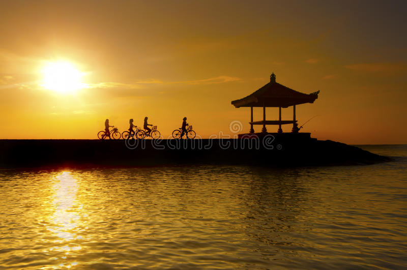 Image of cyclists riding on a concrete barrier in bali indonesia Sanur beach stock photos