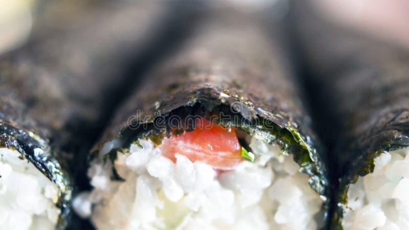 Image détaillée des sushi Rolls avec Nori Seaweed, les poissons rouges et le cachetage de riz sur le conseil avant le découpage e photo libre de droits