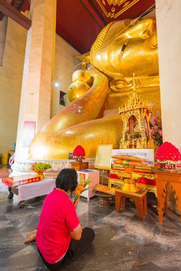 Image d'or étendue adorante de Bouddha de femme rouge de chemise photographie stock