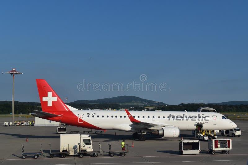 Image d'aiplane de Helvetic sous l'opération de logistique sur le macadam photos stock