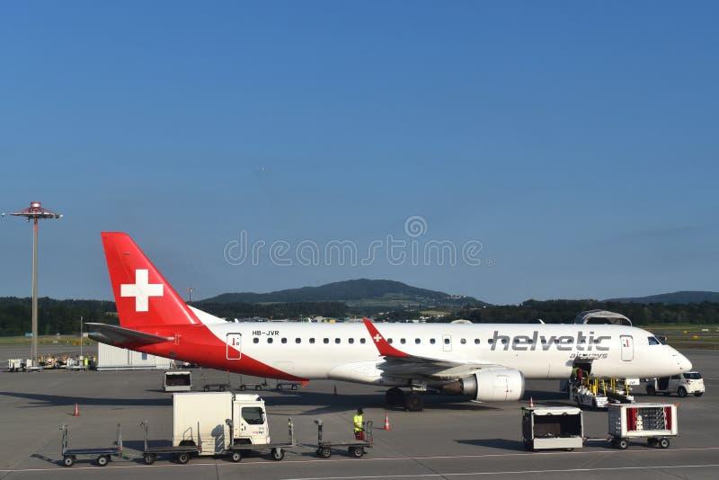 Image d'aiplane de Helvetic sous l'opération de logistique sur le macadam image libre de droits