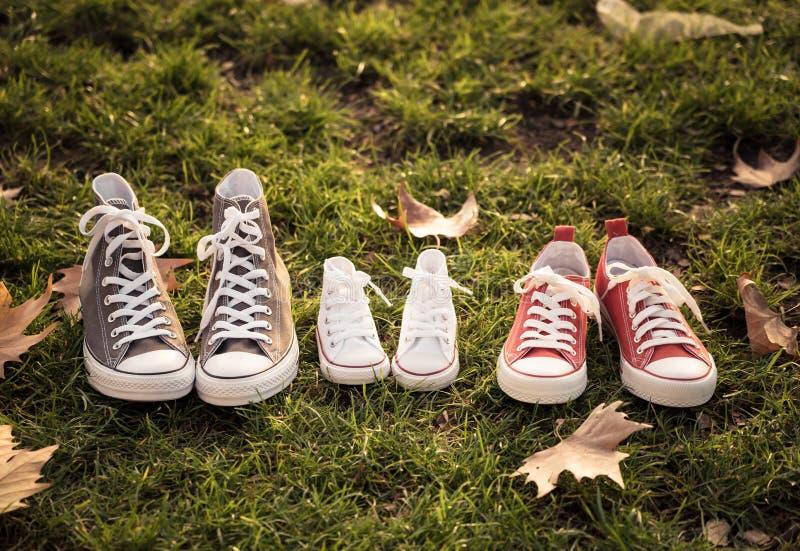 Image d'automne des chaussures en caoutchouc d'espadrilles de chaussures de famille sur l'herbe dans la lumière de coucher du sol photo libre de droits