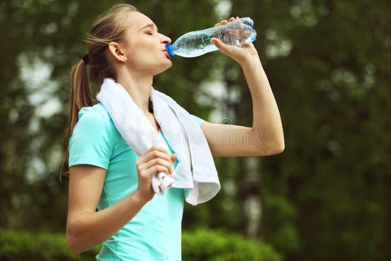 Image d'eau potable de jeune femme images libres de droits