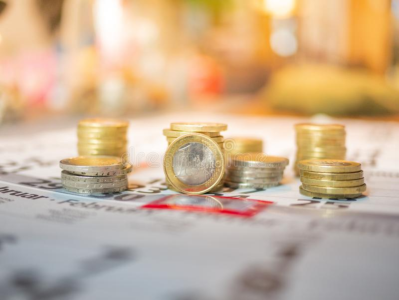 Image d'euro piles de pièce de monnaie sur le calendrier indiquant le jour de salaire photos libres de droits