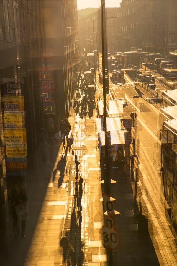 Image d'exposition multiple de la route de York au coucher du soleil Autobus, voitures et personnes de marche contre du soleil Lo image stock