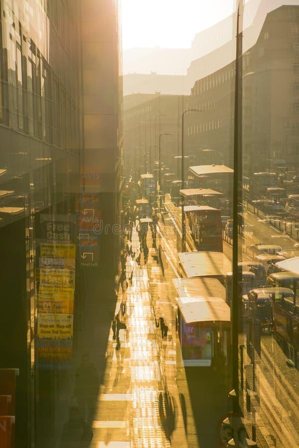 Image d'exposition multiple de la route de York au coucher du soleil Autobus, voitures et personnes de marche contre du soleil Lo photo stock