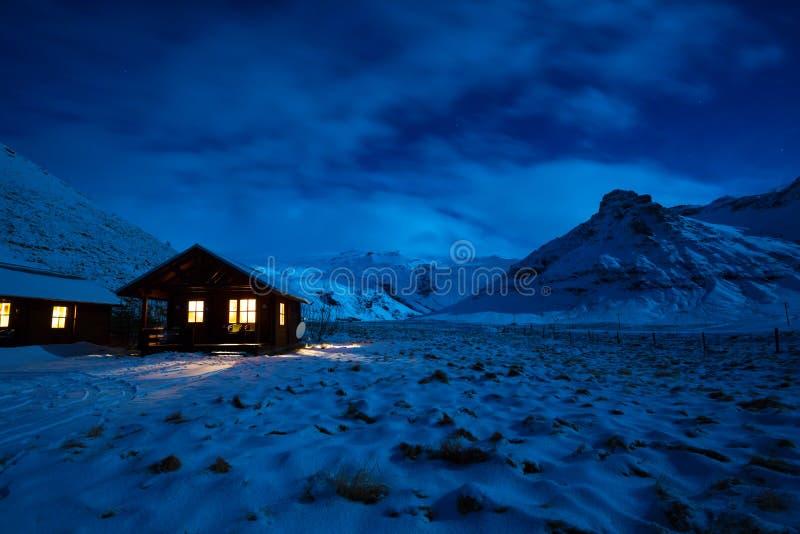Image d'hiver d'une maison en bois avec la lumière de la fenêtre Paysage avec le clair de lune sur la neige avec des montagnes à  images stock