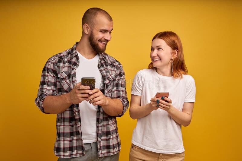 Image d'homme et de femme gais utilisant des smartphones ensemble d'isolement au-dessus du fond jaune images stock