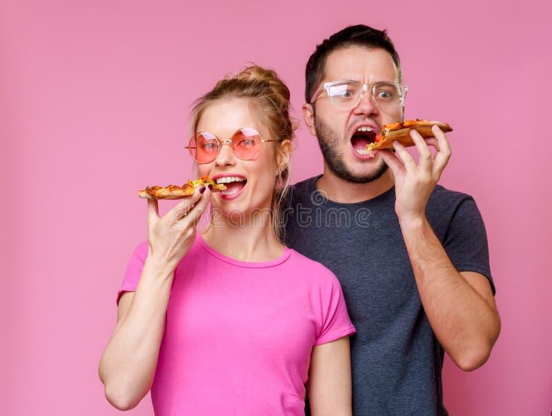 Image d'homme et de femme heureux avec la pizza dans des mains photographie stock libre de droits