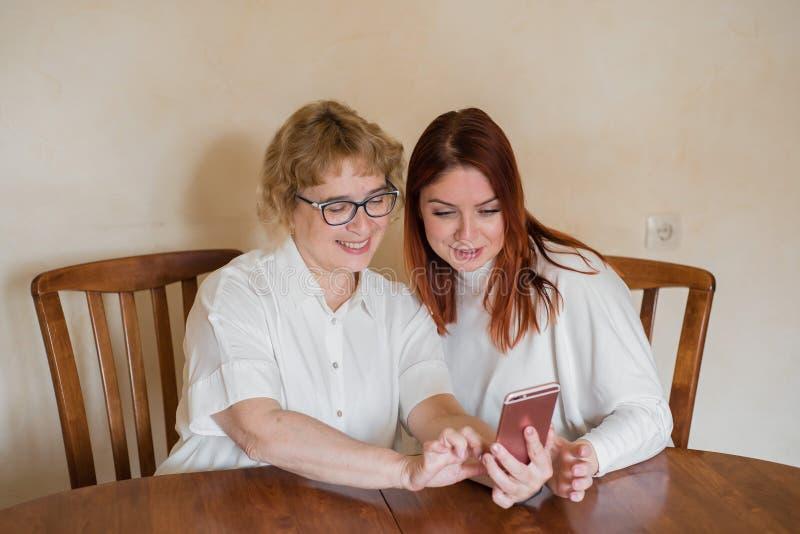 Image d'intérieur d'une belle jeune femme rousse tenant un téléphone portable, montrant à sa mère pluse âgé attirante comment emp photos stock