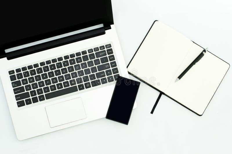 Image d'ordinateur portable d'ordinateur, téléphone portable, carnet vide sur le lieu de travail images libres de droits