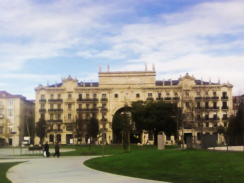 Image d'un bâtiment de cinq étages contre un ciel bleu et une grande pelouse verte photographie stock libre de droits