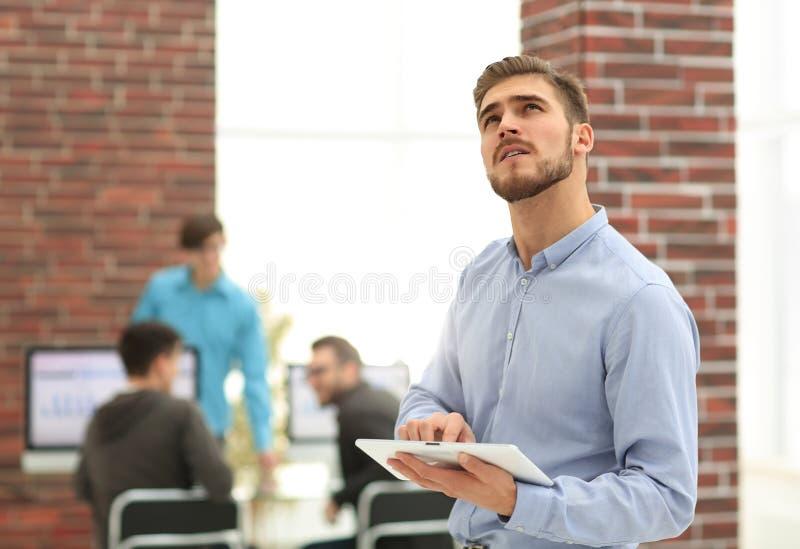 Image d'un homme d'affaires gai travaillant à un comprimé dans l'offic photo libre de droits