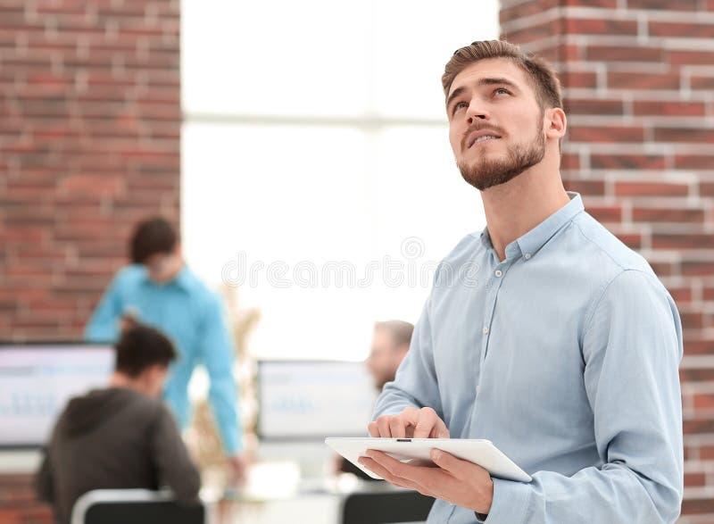 Image d'un homme d'affaires gai travaillant à un comprimé dans l'offic photographie stock