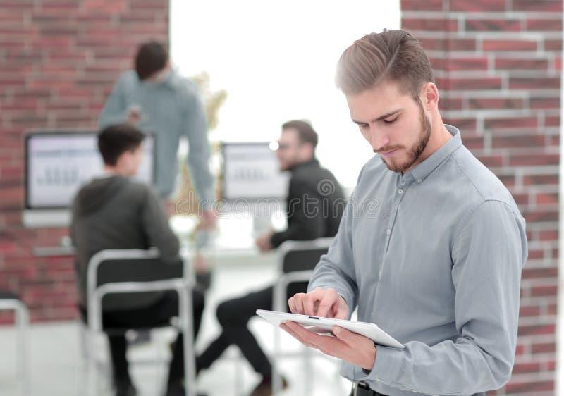 Image d'un homme d'affaires gai travaillant à un comprimé dans l'offic photos stock