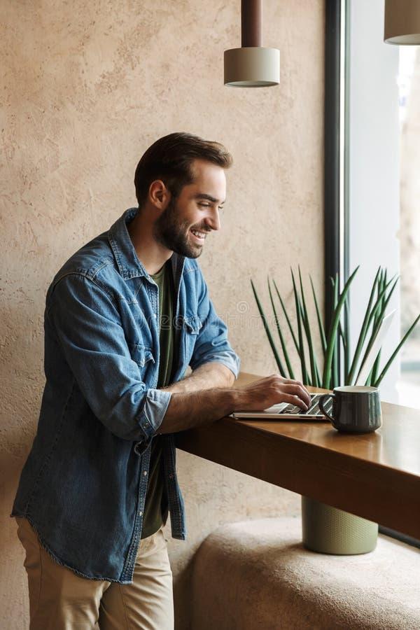 Image d'un homme joyeux souriant et utilisant un ordinateur portable pendant qu'il travaillait dans un café à l'intérieur images stock