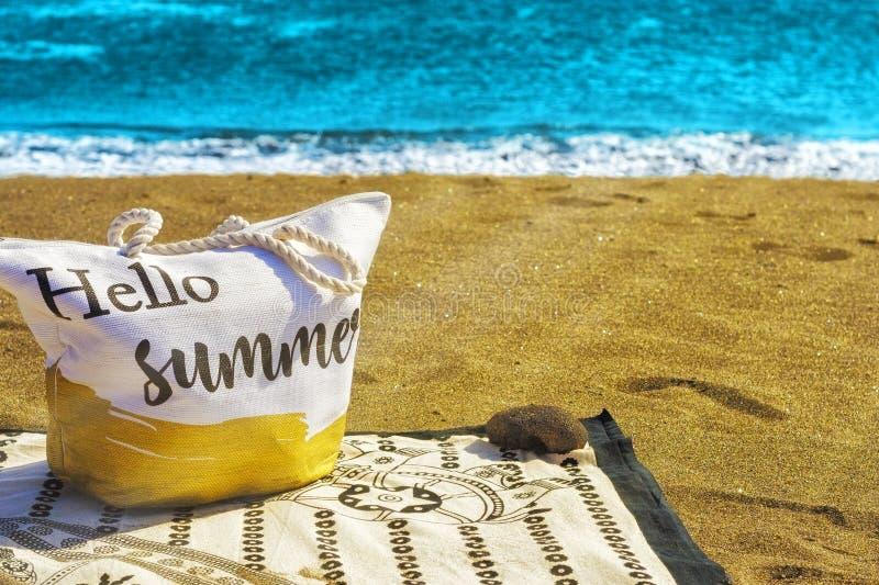 Image d'un sac de plage sur une serviette donnant sur la mer et les rayons de soleil sur lesquels pour mettre bonjour l'?t? image libre de droits
