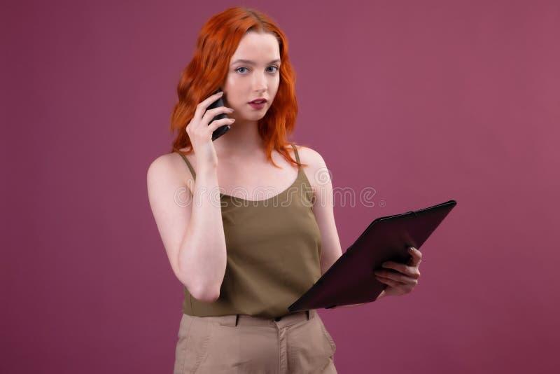 Image d'une belle femme rousse ?tonnante posant au-dessus du dossier rose de participation de fond parlant par le t?l?phone porta image stock