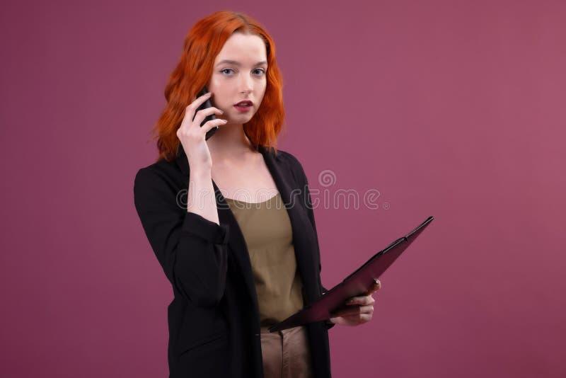 Image d'une belle femme rousse ?tonnante posant au-dessus du dossier rose de participation de fond parlant par le t?l?phone porta photos stock