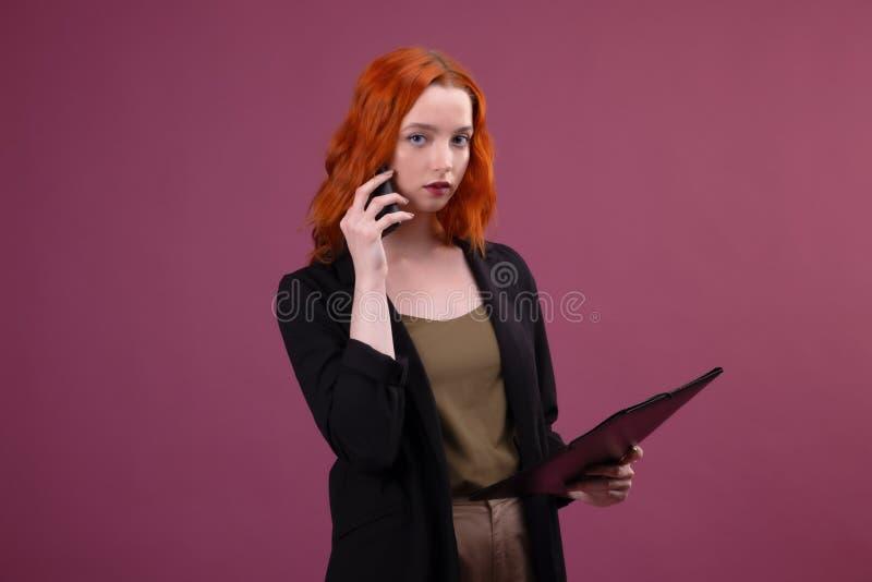 Image d'une belle femme rousse ?tonnante posant au-dessus du dossier rose de participation de fond parlant par le t?l?phone porta photographie stock libre de droits