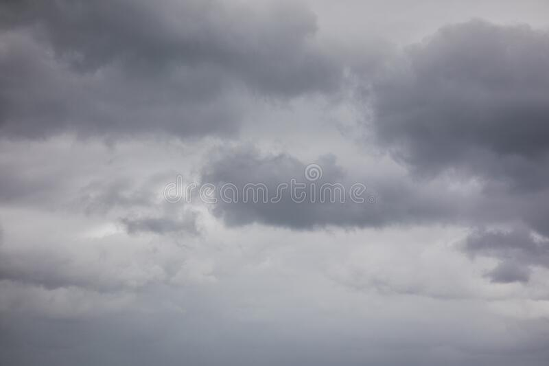 Dark stormy clouds in the sky. A image of a dark stormy sky with patches of dark clouds containing rain royalty free stock image