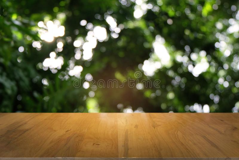 Image of dark wooden table in front of abstract blurred background of outdoor garden lights. can be used for display or montage y royalty free stock photo