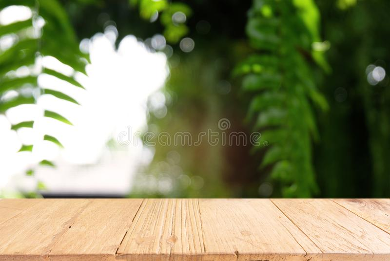Image of dark wooden table in front of abstract blurred background of outdoor garden lights. can be used for display or montage y stock photos